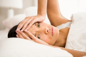 A woman laying in bed with her hands on her head because she's hungover