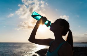 A woman drinking water & staying hydrated after a workout