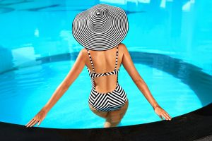 A women in a bathing suit and hat standing in a pool