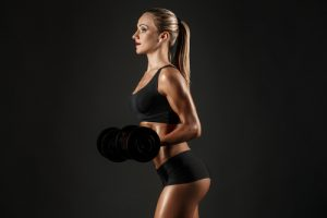 toned woman holding weights